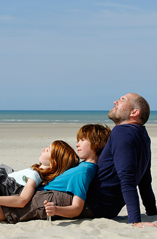 Man and two children sitting together on beach